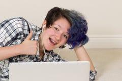 Muchacha adolescente que da los pulgares para arriba mientras que en casa en el ordenador Fotografía de archivo
