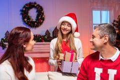 Muchacha adolescente que da presentes a los padres Imágenes de archivo libres de regalías