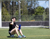 Muchacha adolescente que descansa sobre balón de fútbol mientras que sostiene la botella de agua Fotos de archivo