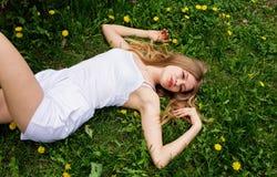 Muchacha adolescente que descansa sobre la hierba Fotos de archivo libres de regalías