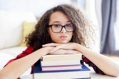 Muchacha adolescente que descansa sobre los libros en el cuarto Imagenes de archivo