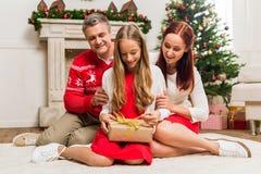 Muchacha adolescente que desempaqueta el regalo de la Navidad Imagenes de archivo