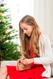 Muchacha adolescente que desempaqueta el regalo de la Navidad Foto de archivo libre de regalías