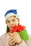 Muchacha adolescente que desgasta el sombrero de Santa con un presente Imagenes de archivo