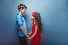 Muchacha adolescente que detiene al adolescente de las manos en gris Imagen de archivo