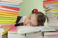 Muchacha adolescente que duerme en la pila de libros Fotografía de archivo libre de regalías