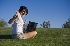 Muchacha adolescente que escucha en su computadora portátil Foto de archivo