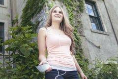 Muchacha adolescente que escucha la música con auriculares de botón de Imagenes de archivo