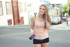Muchacha adolescente que escucha la música con auriculares de botón de Fotografía de archivo