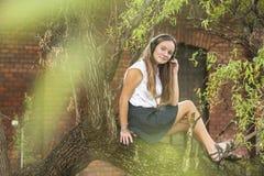 Muchacha adolescente que escucha la música con los auriculares mientras que se sienta en un árbol Foto de archivo