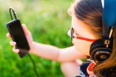 Muchacha adolescente que escucha la música con sus auriculares al aire libre Imagen de archivo libre de regalías