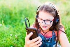 Muchacha adolescente que escucha la música con sus auriculares al aire libre Foto de archivo