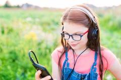 Muchacha adolescente que escucha la música con sus auriculares al aire libre Fotos de archivo