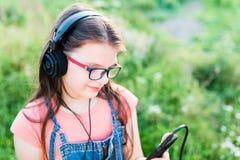 Muchacha adolescente que escucha la música con sus auriculares al aire libre Imagenes de archivo