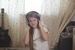 Muchacha adolescente que escucha la música en auriculares en casa Foto de archivo