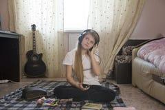 Muchacha adolescente que escucha la música en auriculares usando smartphone y sentarse de dibujo en el piso en casa Imágenes de archivo libres de regalías