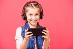 Muchacha adolescente que escucha la música en auriculares y que lleva a cabo el smartphon Imagen de archivo