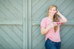 Muchacha adolescente que escucha la música en su teléfono elegante Imagen de archivo libre de regalías