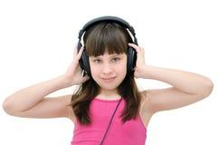 Muchacha adolescente que escucha los auriculares, aislados en el fondo blanco Fotos de archivo