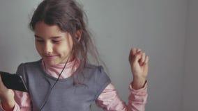 Muchacha adolescente que escucha los auriculares de la música y que baila en un smartphone Foto de archivo libre de regalías