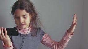 Muchacha adolescente que escucha los auriculares de la música y que baila en un smartphone Imagen de archivo libre de regalías
