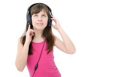 Muchacha adolescente que escucha los auriculares, en el fondo blanco Imágenes de archivo libres de regalías