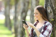Muchacha adolescente que escucha y que elige música Imágenes de archivo libres de regalías