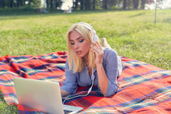 Muchacha adolescente que estudia con un ordenador portátil en el prado en parque Fotografía de archivo