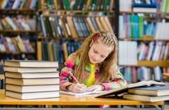 Muchacha adolescente que estudia en la biblioteca Fotografía de archivo
