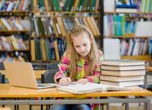 Muchacha adolescente que estudia en la biblioteca Foto de archivo libre de regalías