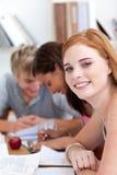 Muchacha adolescente que estudia en la biblioteca con sus amigos Fotos de archivo libres de regalías