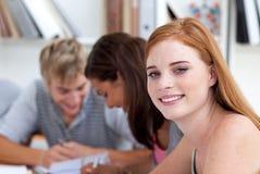 Muchacha adolescente que estudia en la biblioteca con sus amigos Imágenes de archivo libres de regalías