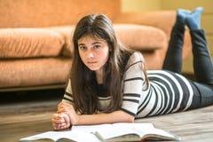 Muchacha adolescente que estudia la mentira en el piso Educación Imagenes de archivo