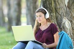 Muchacha adolescente que estudia tutoriales video de observación Foto de archivo libre de regalías