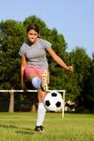 Muchacha adolescente que golpea el balón de fútbol con el pie Fotografía de archivo libre de regalías