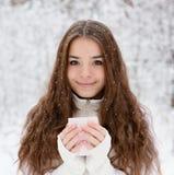 Muchacha adolescente que goza de la taza grande de bebida caliente durante día frío Fotos de archivo libres de regalías