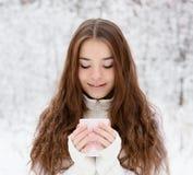 Muchacha adolescente que goza de la taza grande de bebida caliente durante día frío Imagen de archivo libre de regalías
