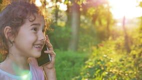 Muchacha adolescente que habla en el teléfono en una naturaleza verde del fondo al aire libre almacen de video