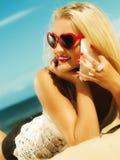 Muchacha adolescente que habla en el teléfono móvil en la playa Foto de archivo libre de regalías