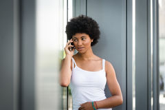 Muchacha adolescente que habla a su amigo en el teléfono Fotos de archivo