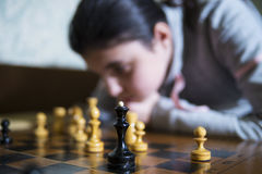 Muchacha adolescente que hace el jaque mate que juega a ajedrez Foto de archivo libre de regalías
