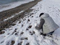 Muchacha adolescente que hace el muñeco de nieve en la playa del invierno Foto de archivo libre de regalías