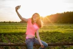 Muchacha adolescente que hace el selfie en el teléfono en fondo de la puesta del sol Imagen de archivo libre de regalías