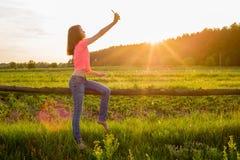 Muchacha adolescente que hace el selfie en el teléfono en fondo de la puesta del sol Imagenes de archivo