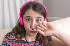 Muchacha adolescente que hace gesto del bigote con su finger en el sofá en el hom Fotografía de archivo