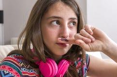 Muchacha adolescente que hace gesto del bigote con su finger en el sofá en el hom Imagenes de archivo