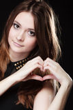 Muchacha adolescente que hace símbolo del amor de la forma del corazón con las manos Imagenes de archivo