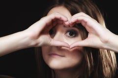 Muchacha adolescente que hace símbolo del amor de la forma del corazón con las manos Imagen de archivo libre de regalías