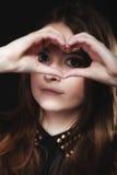 Muchacha adolescente que hace símbolo del amor de la forma del corazón con las manos Imágenes de archivo libres de regalías