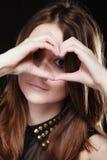 Muchacha adolescente que hace símbolo del amor de la forma del corazón con las manos Foto de archivo